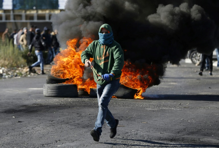 A masked Palestinian protester runs during clashes with Israeli troops in the West Bank city of Ramallah.